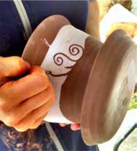 milly doing sgraffito on a pot